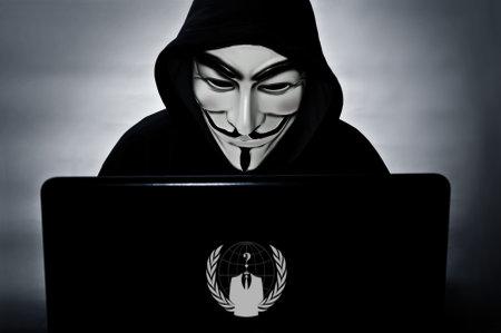 París - Francia - 25 de enero 2015 - miembro anónimo con la computadora con la máscara de la venganza el símbolo del grupo hacktivista Anonymus Editorial