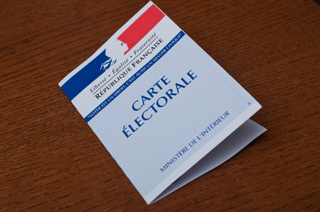 PARIS - France - 15 March 2015 - french electoral card on wooden background Editorial