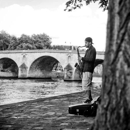 saxophonist: PARIS - France - 21 June 2012 - saxophonist in border Seine river in Paris Editorial