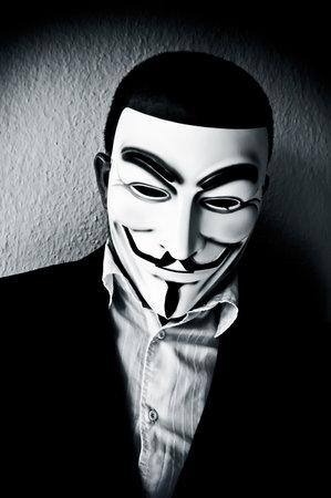 파리 - 프랑스 - 2211 년 4 월 22 일 - 남자 양복 사업가 및 Vendetta 마스크를 착용. 이 가면은 온라인 hacktivist 그룹을위한 유명한 상징이다 Anonymous 에디토리얼
