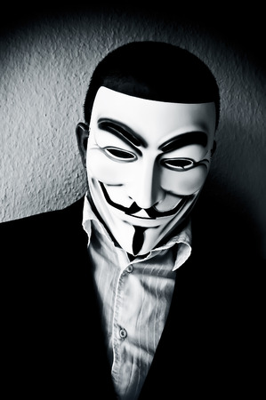 PARIS - France - 22 April 2015 - man wearing suit businessman and Vendetta mask. This mask is a well-known symbol for the on line hacktivist group Anonymous