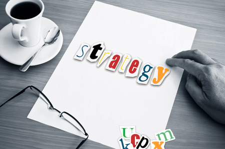 concept office cup of coffee and word strategy on white page Stockfoto