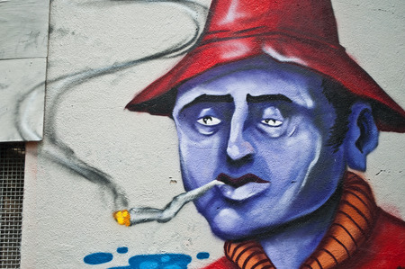 sinners: MULHOUSE - France - 08 June 2015 - graffiti of a sick man with cigarette during the BOZAR graffiti festival - quay of sinners in Mulhouse Editorial