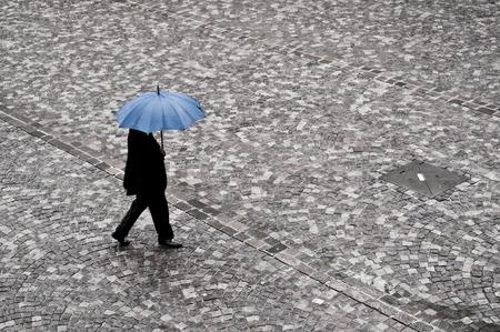 자갈길 된 장소에 푸른 우산과 함께 비가 깨어 사업가