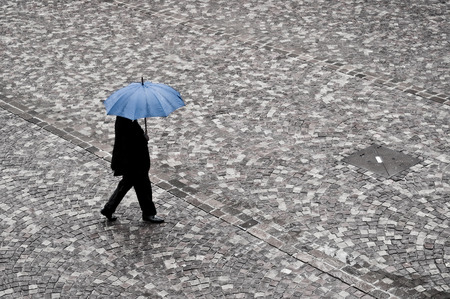 businessman waking in the rain with blue umbrella on cobbled place