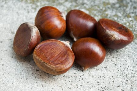 stoned: closeup group of chestnuts on stoned background Stock Photo