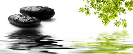 Regendruppels op zwarte kiezelstenen in grenswater reflectie Stockfoto - 48060262
