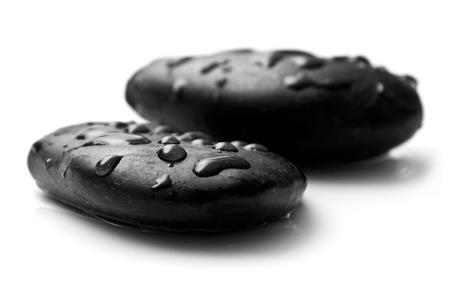 black pebbles: raindrops on black pebbles on white background Stock Photo