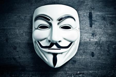 파리 - 프랑스 - 2011 년 11 월 8 일 - 목조 배경에 Vendetta 마스크. 이 마스크는 온라인 hacktivist 그룹 Anonymous의 잘 알려진 상징입니다. 에디토리얼