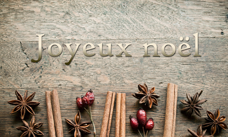christmas perfume: decorative anise cinnamon and dog rose on wooden background (text in french)