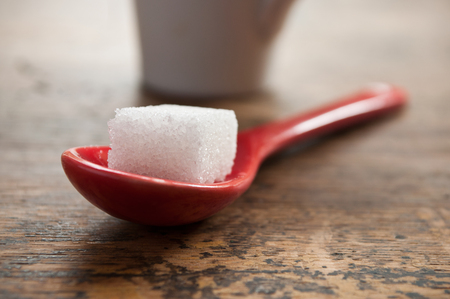 closeup of sugar cube in a red spoon on wooden background