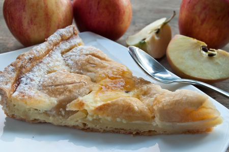 closeup of apple pie with raw apples on wooden table Stock Photo