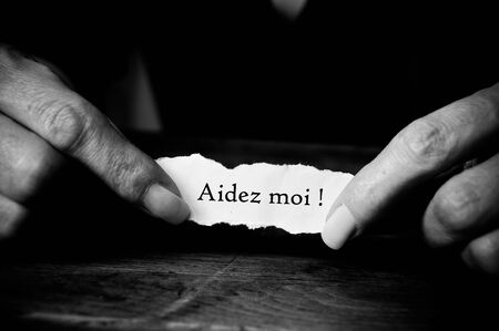 battered: Concept  oman with message on paper in hands - Aidez moi  Help me in french Stock Photo