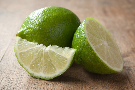 closeup of green lemon on wooden background