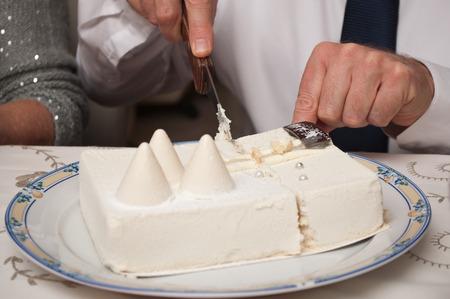 snow man party: closeup of man cutting christmas ice cream cake