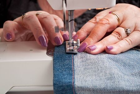 closeup of woman with a sewing machine and blue jeans hem Stock Photo