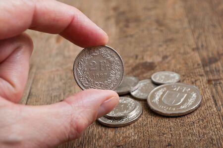 helvetia: Coins of Switzerland in hand on wooden desk