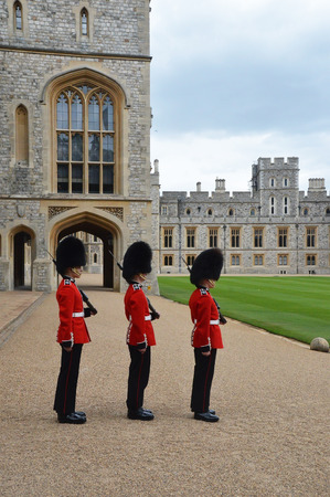 beefeater: LONDON - ENGLAND JUNE 02 2015 : windsor castle - The Queens Guards are the contingents of infantry and cavalry soldiers charged with guarding the official royal residences.