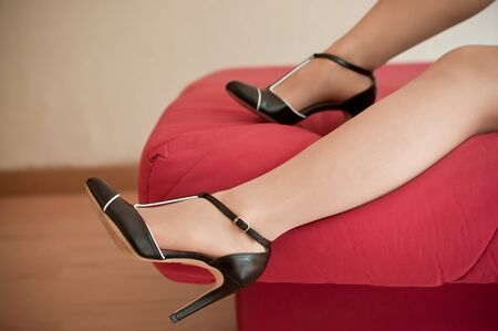red bed: closeup of woman with stilettos shoes on red bed