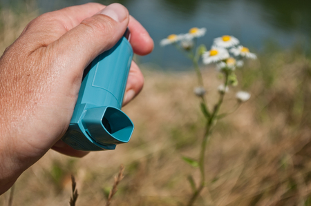 closeup of hand with asthma aerosol in outdoor near flowers Stock Photo