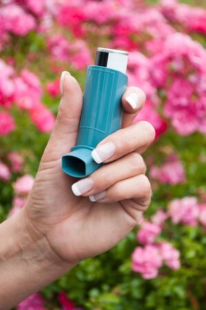 closeup of hand of woman with asthma aerosol in outdoor near pink flowers