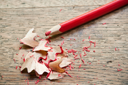 shavings: red pencil and shavings on wooden background