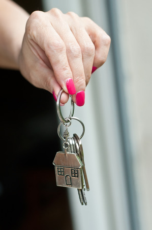 closeup of woman giving metallic key with house shaped key chain to lodger Stock Photo