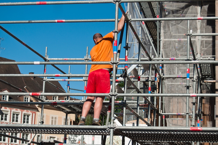 reinforcement: worker on scafold on renovation site