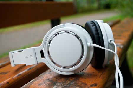 closeup of white headphones on bench in outdoor Stock Photo