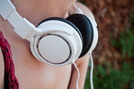 closeup of woman with white headphones in outdoor Stock Photo