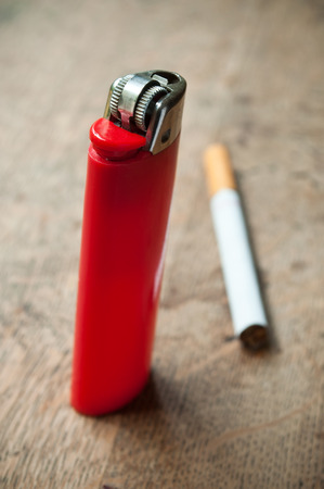 closeup of red lighter and cigarette on wooden background