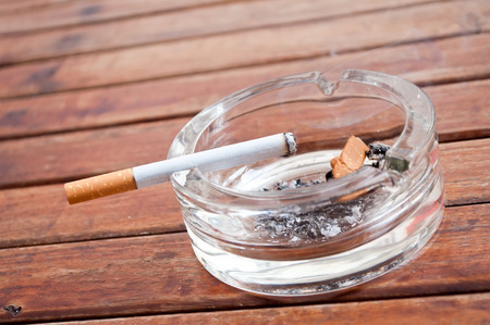 closeup of  cigarette on the edge of the  ashtray on wooden table