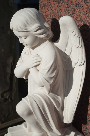 angel cemetery: stoned angel in cemetery on a tomb Stock Photo