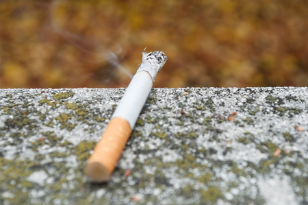 ashes: closeup of  cigarette resting on a wall Stock Photo