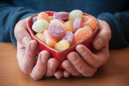 closeup of man hands with a traditional candies in a shaped heart bowl Stock Photo