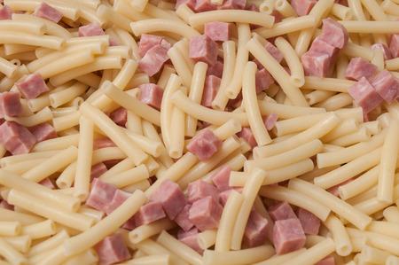 pancetta cubetti: closeup of macaroni pasta with ham cubes texture Archivio Fotografico