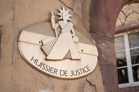 closeup bailiff plate on french building facade - huissier de justice ( text in french) bailiff