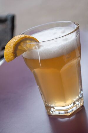 closeup of glass of bier on table with sliced lemon