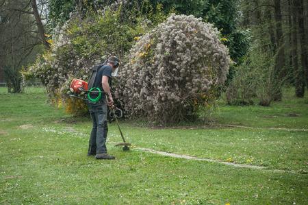 gardener with Brushcutter in a public garden