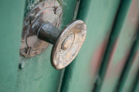 closeup of bronze handle on green metallic door