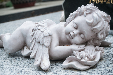 closeup of white angel in cemetery on a tomb