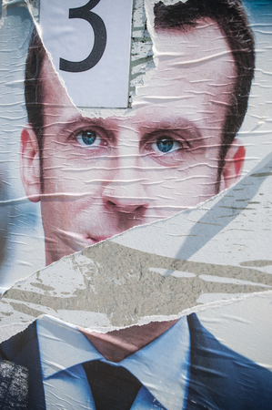 torn metal: MULHOUSE - France - torn poster of Emmanuel Macron the finalist candidate for tre presidential election Editorial