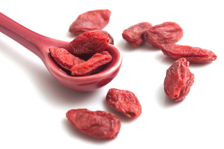 closeup of goji berries in a spoon on white background