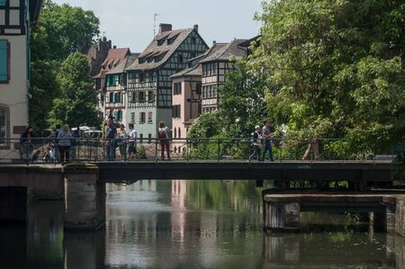 rive: STRASBOURG - France - 25 May 2017 - traditional architecture and metallic bridge on Rhine river at little France quarter in Strasbourg