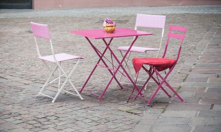 isolated pink metallic table In the middle of a paved square