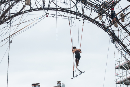 trapeze: MULHOUSE - France - 11 July 2017 - Portrait of a young woman training on trapeze for an outdoor aerobatics show in the main place of Mulhouse Editorial
