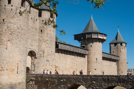 Carcassonne - France - 21 August 2017 - tourists on stone bridge in fortifications entry
