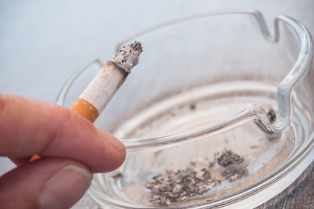 closeup of hand of man with cigarette and ashtray Stock Photo