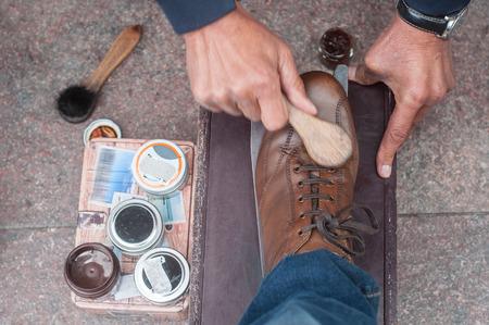 구두의 근접 촬영은 갈색 가죽 신발에 거리에서 빛난다.