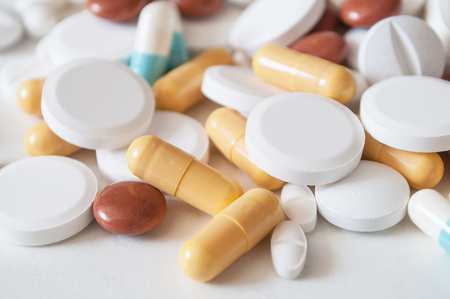 closeup of capsules and drug tablets on white background